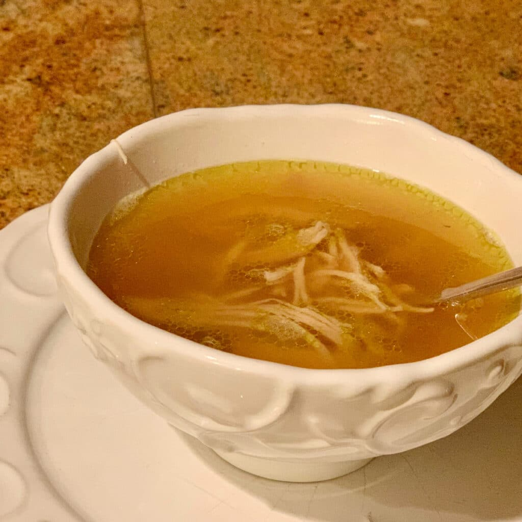 round white bowl on a round white plate filled with golden chicken soup broth and some shredded chicken pieces