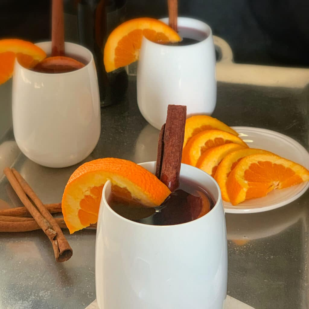 close up of three glasses containing mulled wine with a plate of sliced oranges and cinnamon sticks