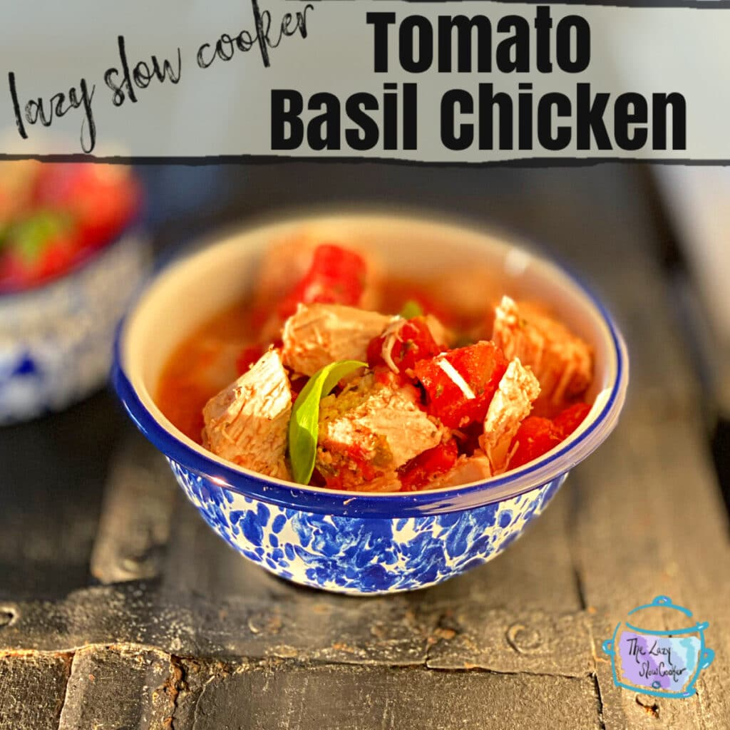 a skinny recipe on a round blue and white bowl on a distressed black surface filled with juicy chunks of chicken and tomato and sprinkled with freshly chopped green basil.