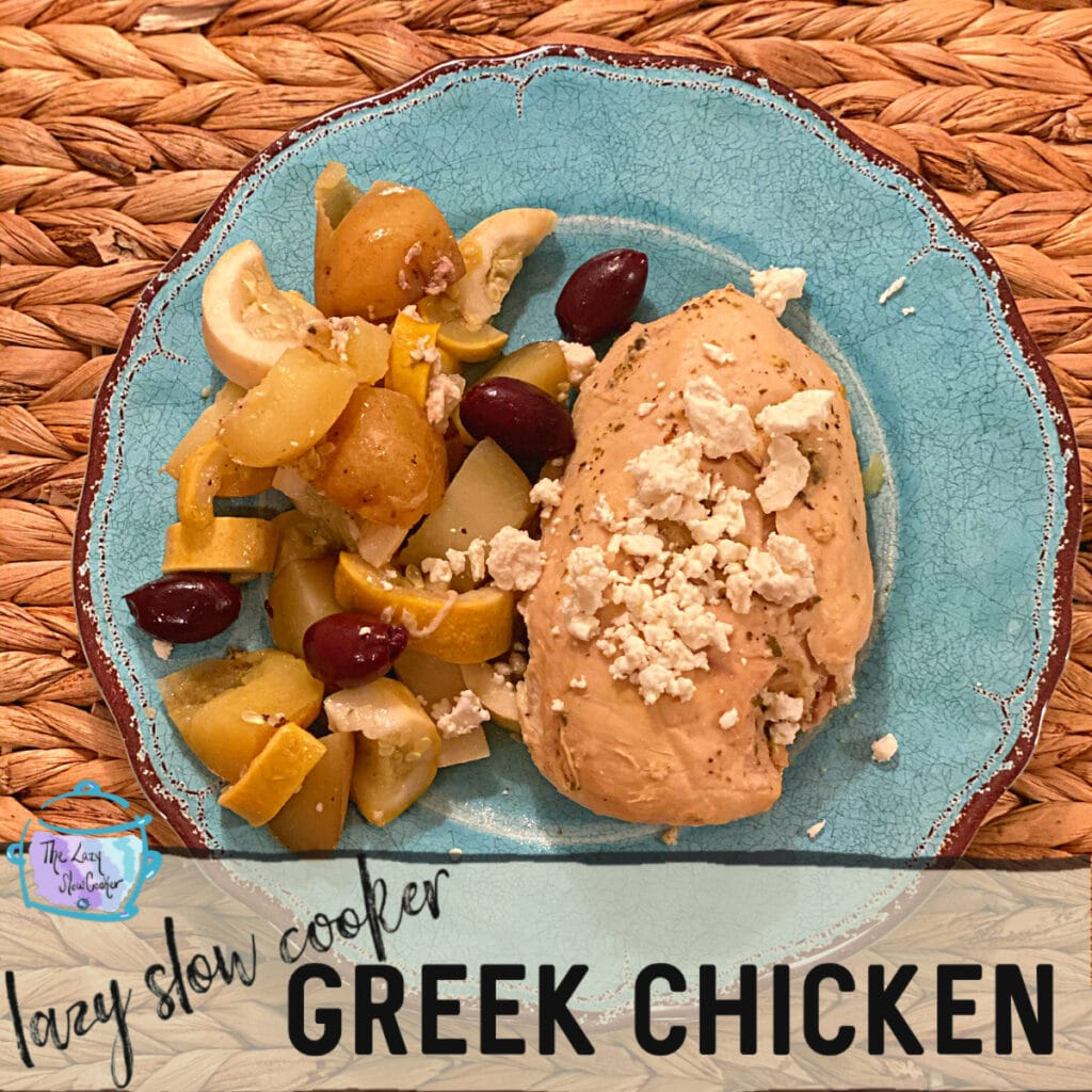 close up of a chicken breast with feta cheese sprinkled on top with cooked veggies and kalamata olives on a turquoise plate