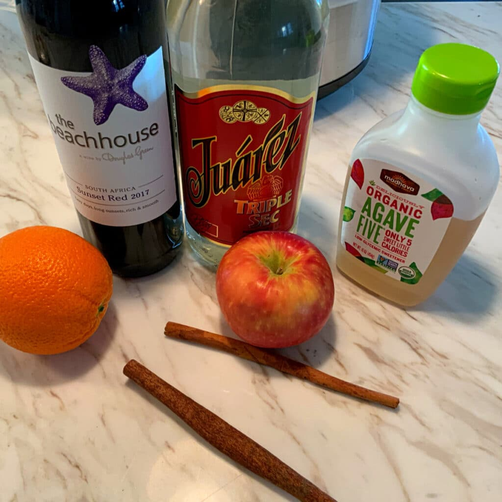 bottle of alcohol, agave and fruits that go into this recipe