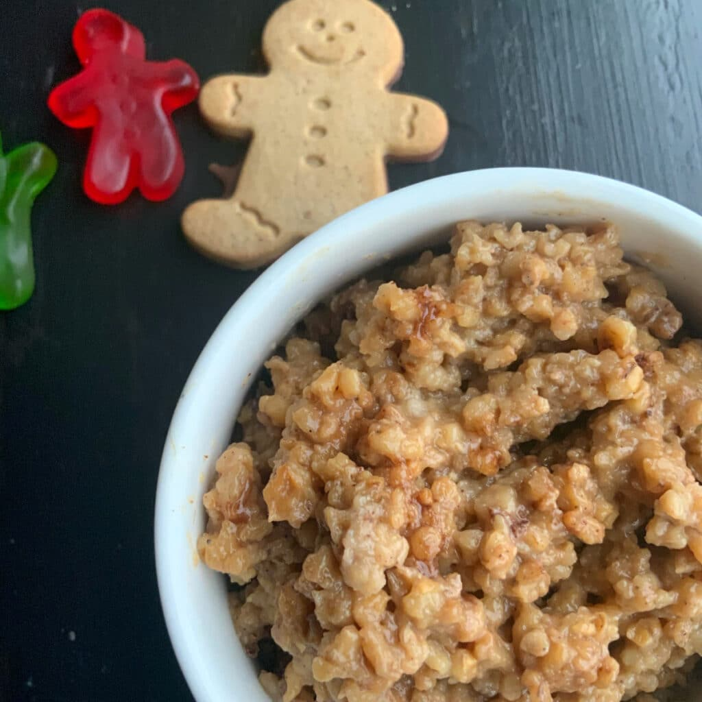 Gingerbread oatmeal with cinnamon sprinkled one top with a cooked and some red and green gingerbread shaped gummies off the side