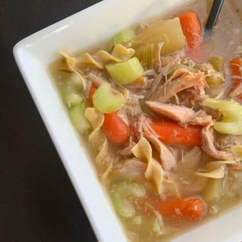 Turkey soup in a square bowl with a black spoon set on an angle. Soup has baby carrots, celery chunks and turkey shreds
