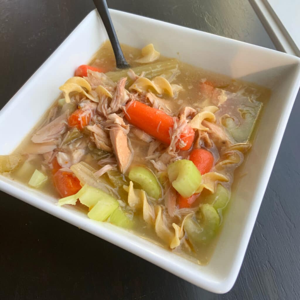 Close up of a bowl of turkey soup filled with carrots, celery, turkey and noodles. A black spoon is sticking out of the white square bowl that is holding the soup