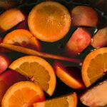 Fruits and cinnamon stick floating in wine and other ingredients