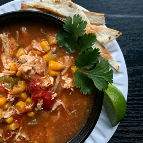 Chicken tortilla soup in a round black bowl garnished with green cilantro, a wedge of lime and some toasted tortilla strips