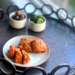 distance view of apricot chicken on a round white plate with broccoli and potatoes in the background