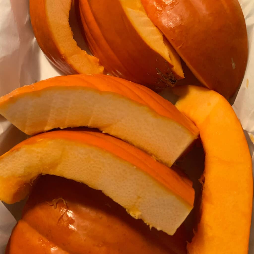 Close up of cut up pumpkin pieces in a white slow cooker