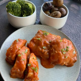 Apricot chicken on a round gray plate with a bowl of mini potatoes and a bowl of broccoli in the background