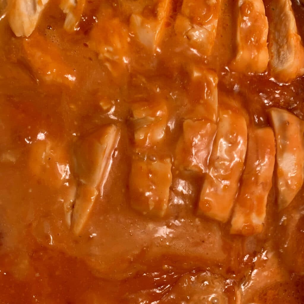 sliced chicken breast put back in sauce in pot