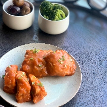 a medium distance view of a plate containing apricot chicken breasts and thighs covered in sauce