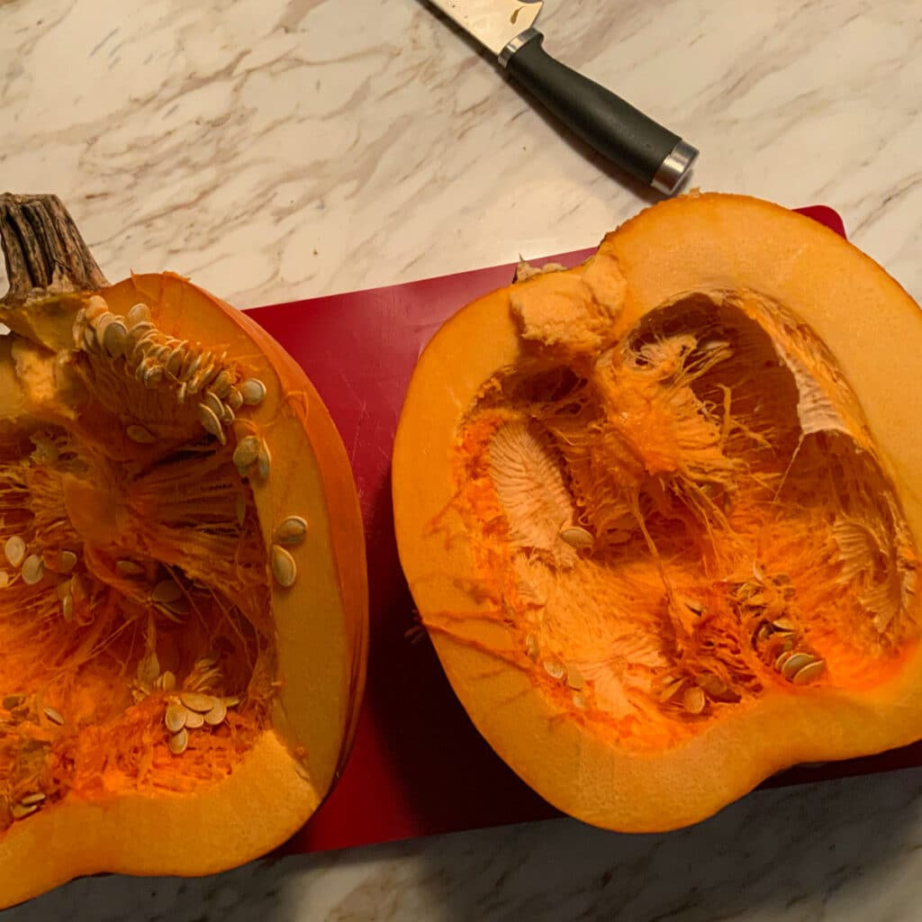 Pumpkin cut in half laying on a red cutting mat with the seeds still inside.