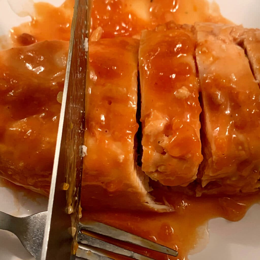 close up of cooked chicken breast with sauce beling sliced by a large knife