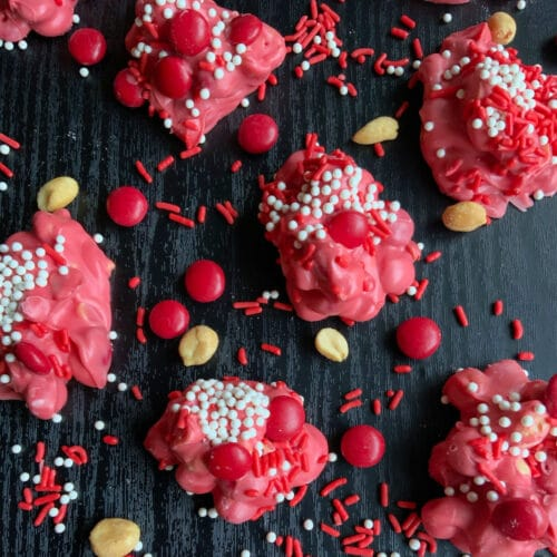 red crockpot candy on a black surface surrounded by sprinkles and nuts