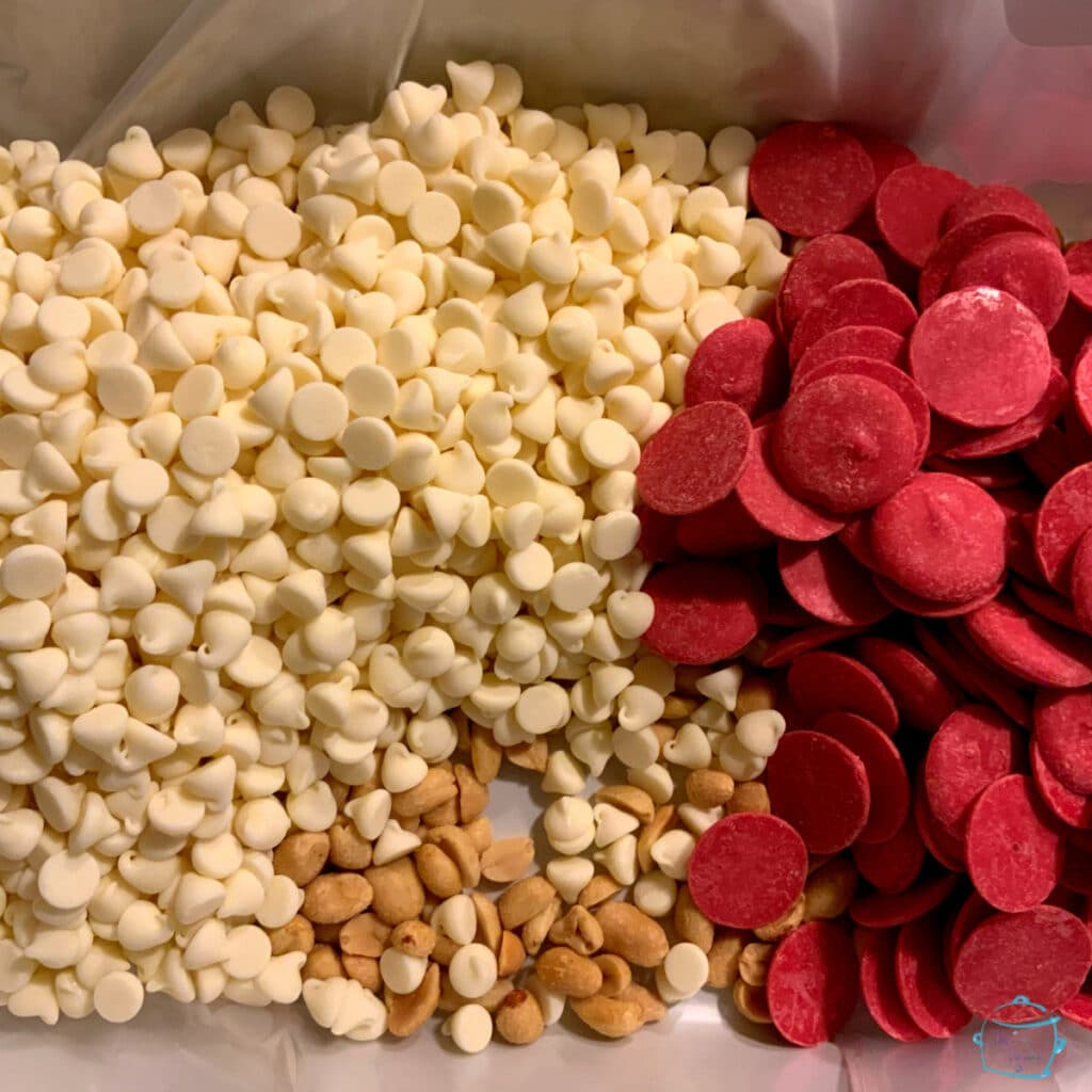 white chocolate morsels peanuts and red candy melting wafers in a slow cooker