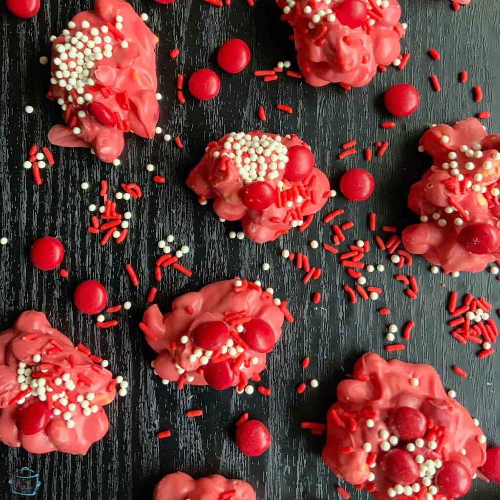 pink chocolate candy with red candy decoration and sprinkles laying all around