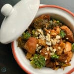 Chicken dish in a round with pot with the lid tilted off to the side. Fresh raw cashews are crumbled on top
