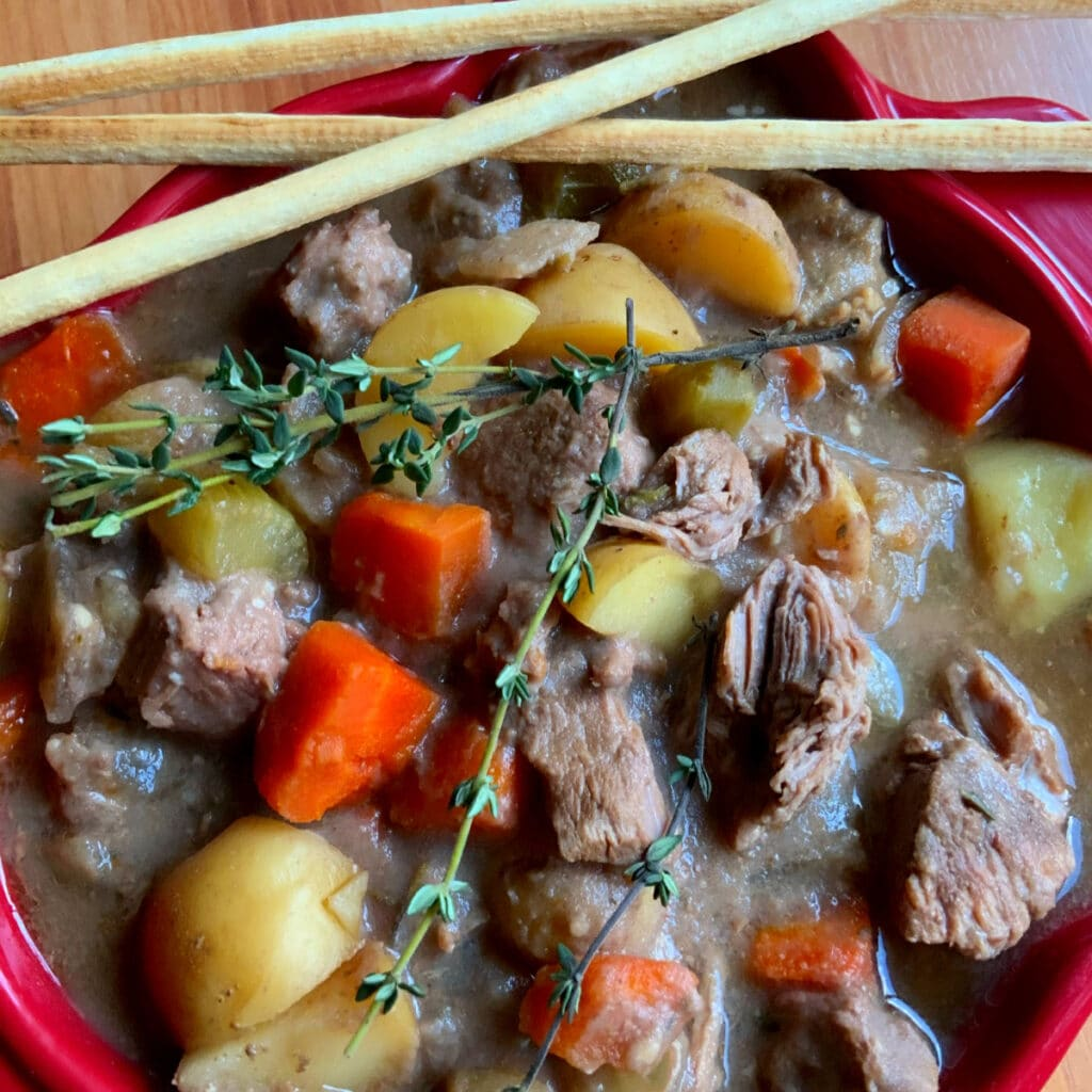 Close up of beef stew in a red square bowl with skinny bread sticks