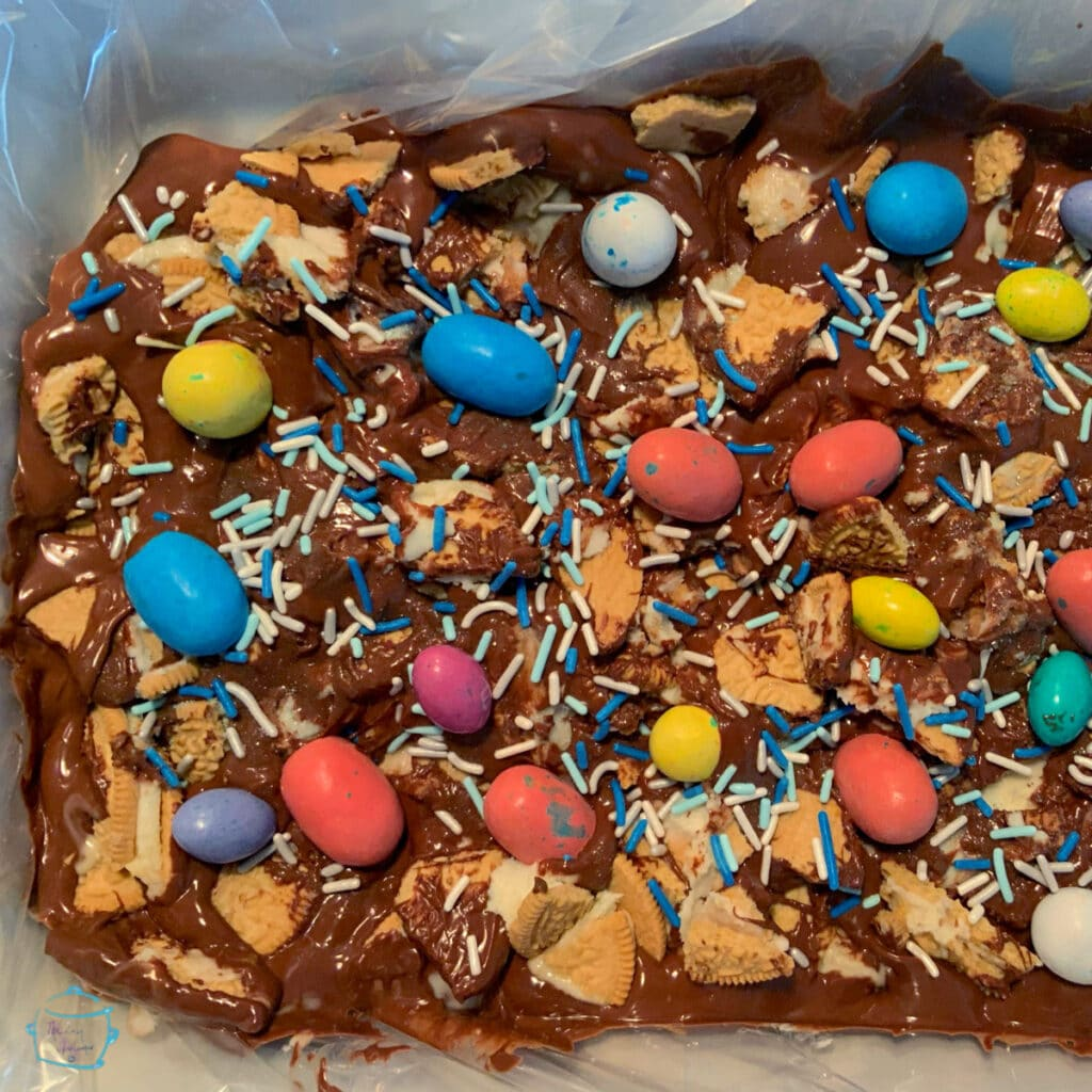 milk chocolate bark in a slow cooker decorated with Easter Eggs and sprinkles