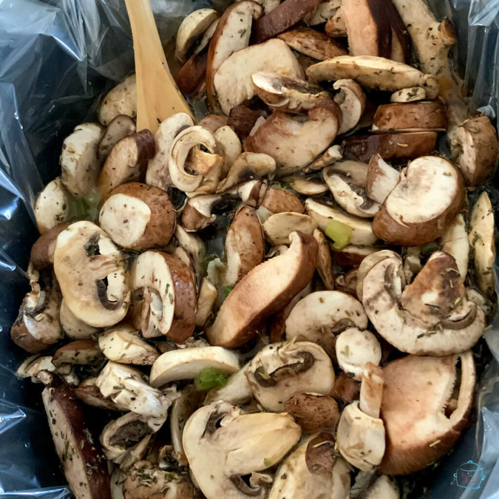 Sliced mushrooms in a crockpot with a wooden spoon