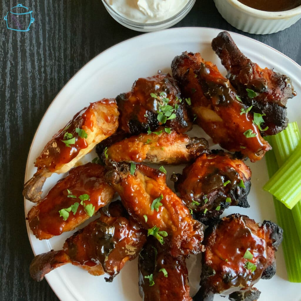 looking down on a plate of crispy, saucy wings with celery on the side