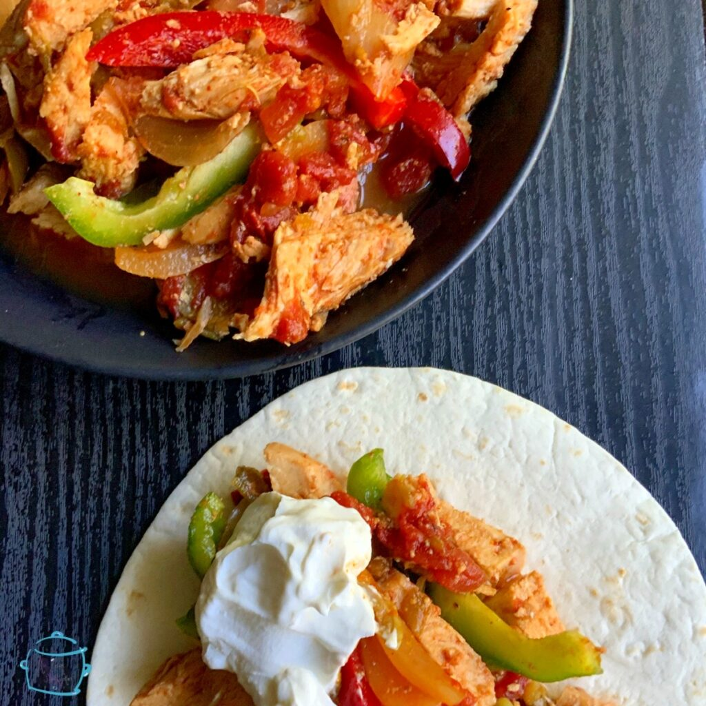 A partial view of a bowl of fajita ingredients next to a tortilla topped with the same