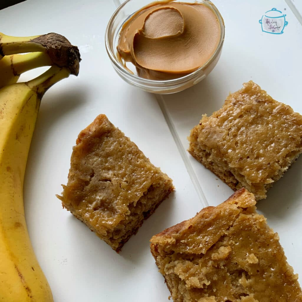 Three pieces of crockpot banana bread next to some peanut butter and bananas