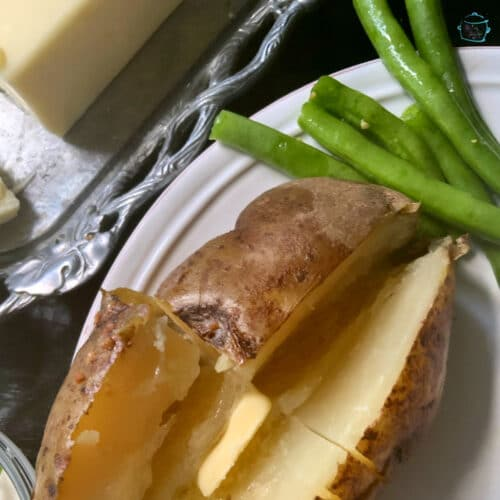 An open baked potato with butter and some bright green beans