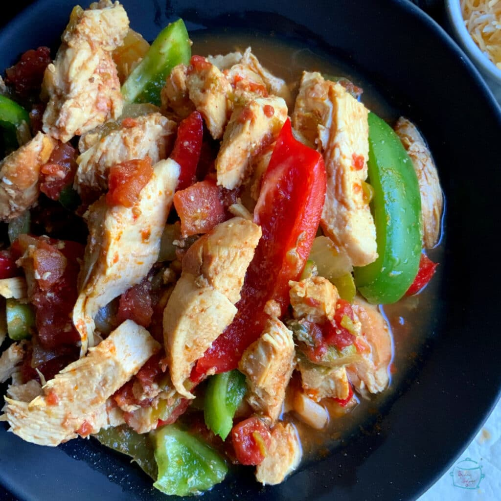 Cooked chicken, peppers and onions in a black bowl