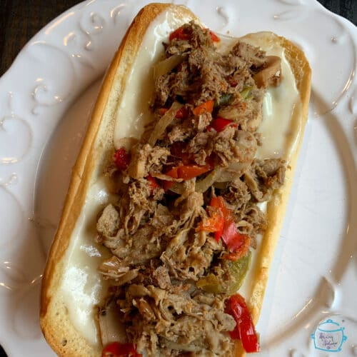 A cheesesteak sandwich laying open on a plate