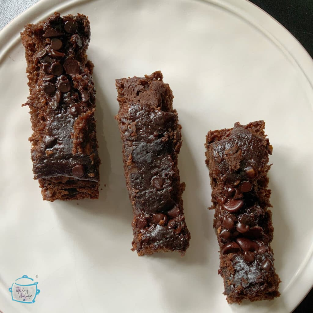 Three pieces of chocolate banana bread in a diagonal line on a plate