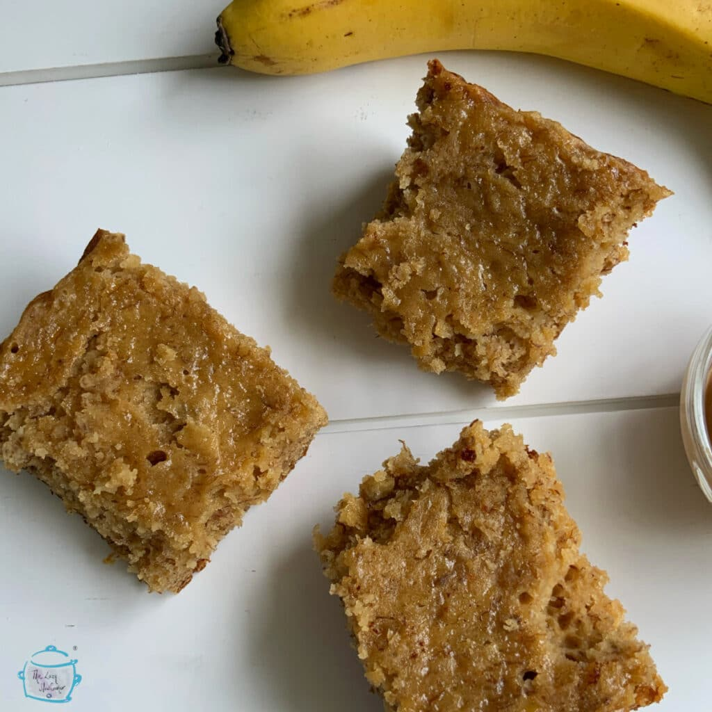 Three pieces of banana bread on a white background with a whole banana