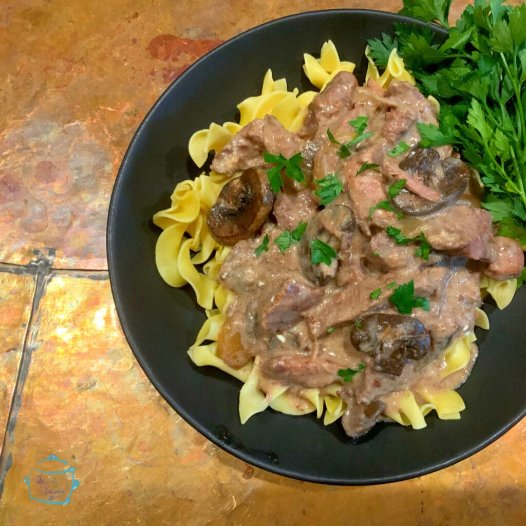 Plated beef stroganoff on noodles with some greens off to the side