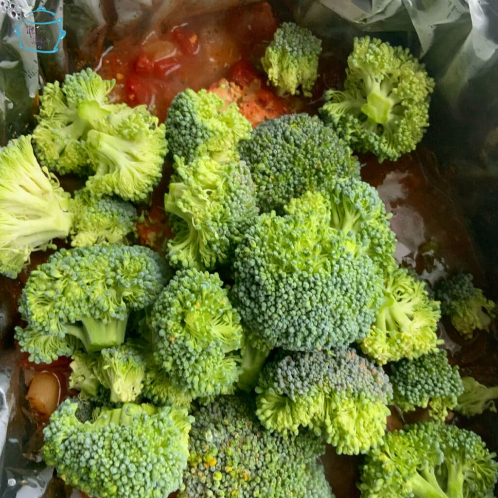 Raw broccoli on top of remaining cooked ingredients