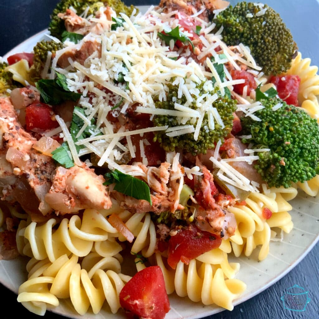 Finished dish plated on pasta topped with parmesan