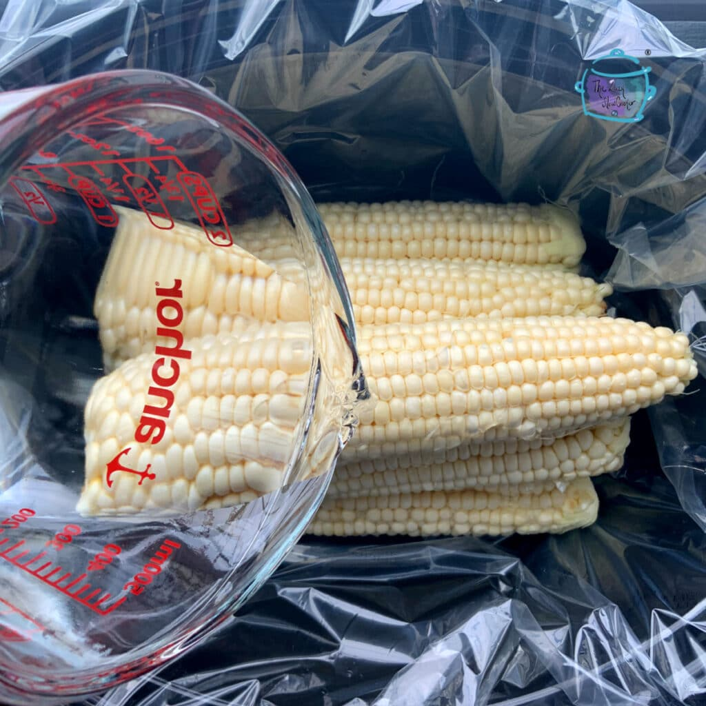 multiple ears of corn in slow cooker with water being added