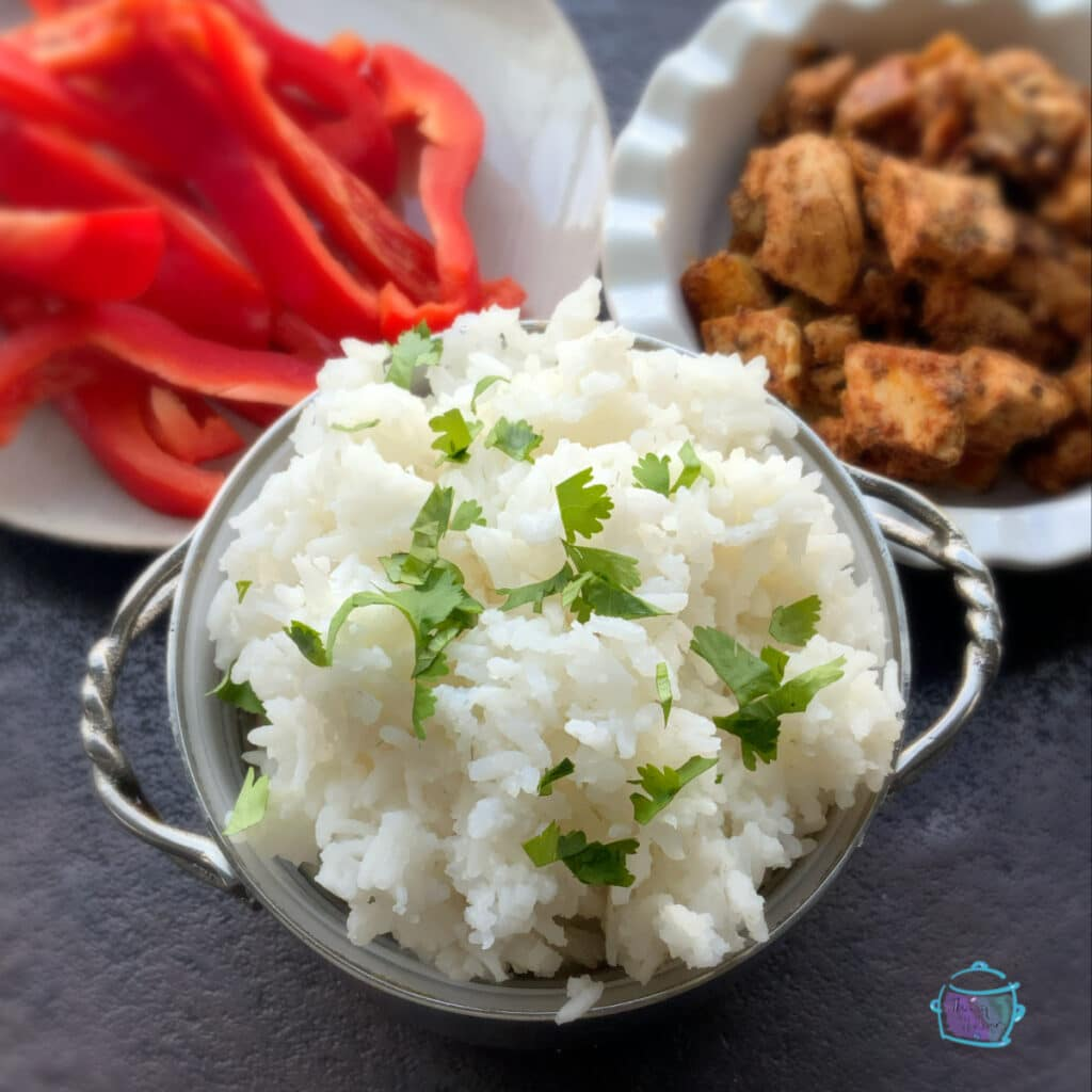 rice with chicken chunks and peppers on side.
