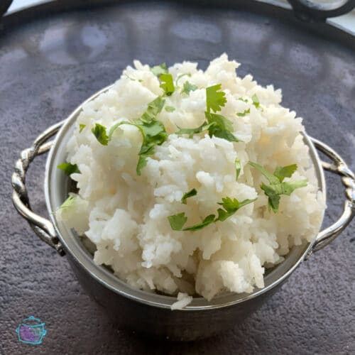 silver bowl of white rice topped topped with fresh chopped cilantro