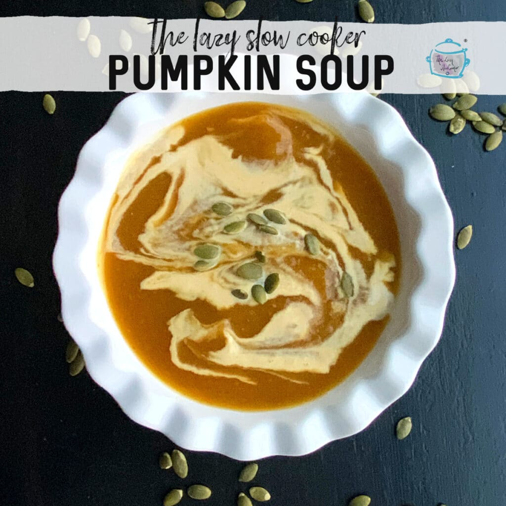 a white bowl with pumpkin soup and some dairy free cream in swirling pattern