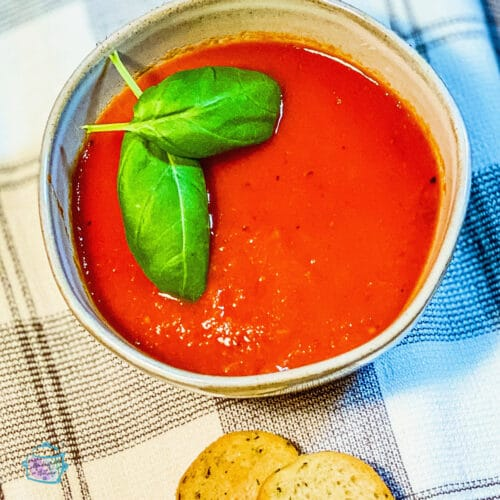 A bowl of tomato soup with basil leaves on top