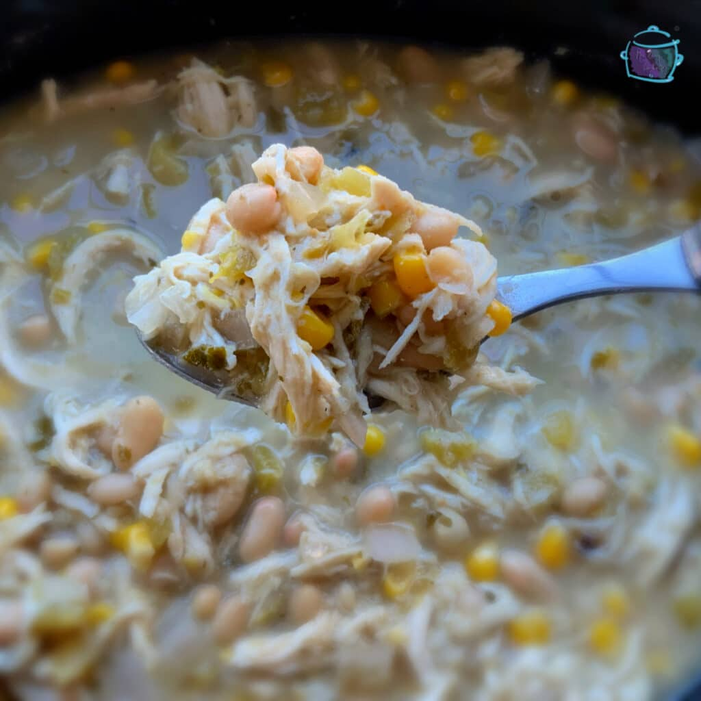 White chicken chili on a spoon held close to the camera with a post of the same in the background