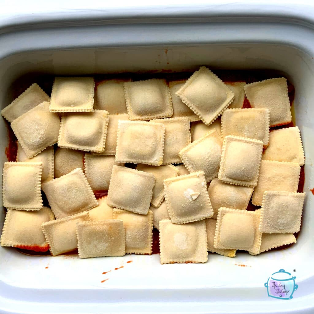 A casserole crockpot with a layer of frozen ravioli on top of red sauce