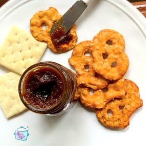 Apple butter with being spread on pretzel flats with other crackers