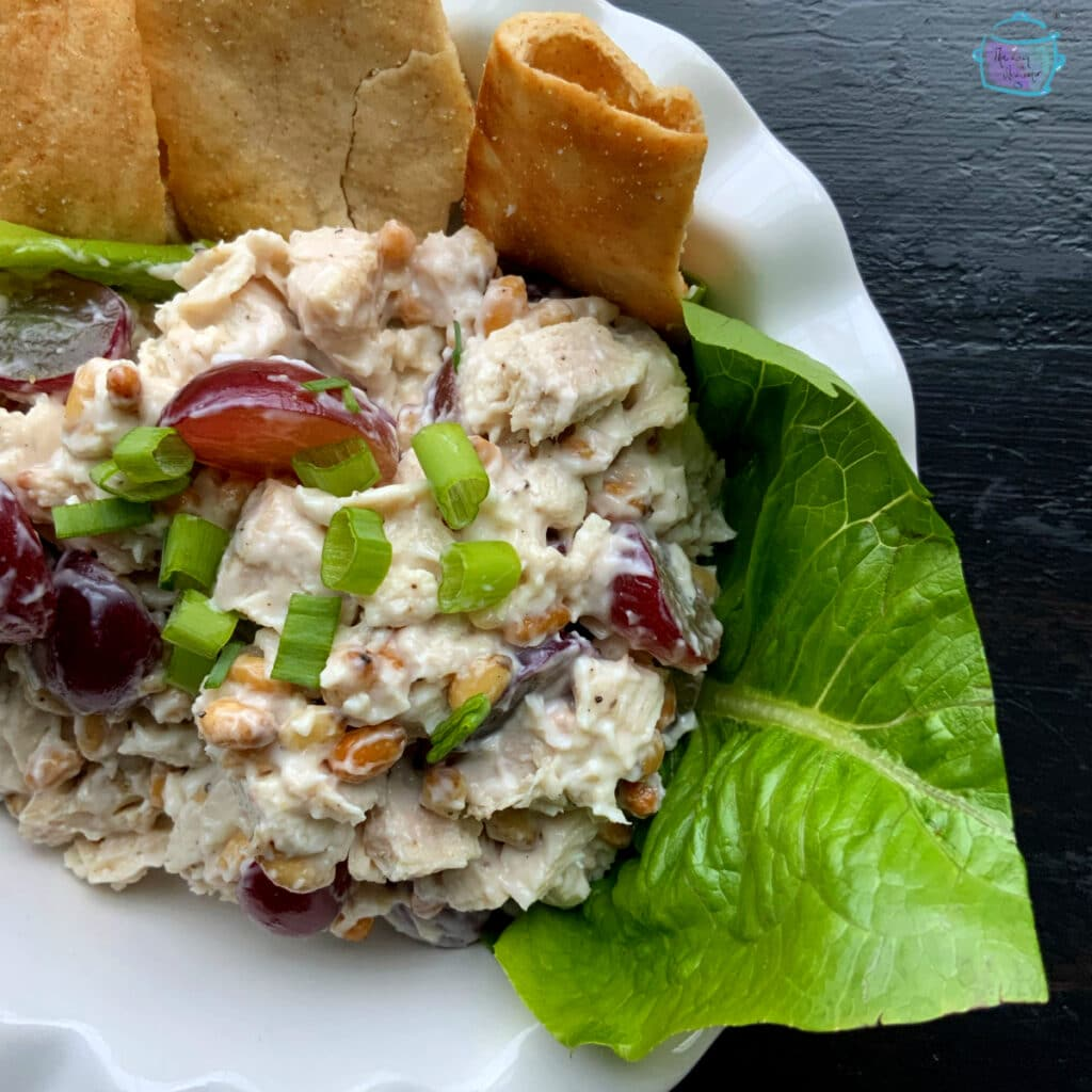 Close up of turkey salad on a lettuce leaf with pita chips on the side